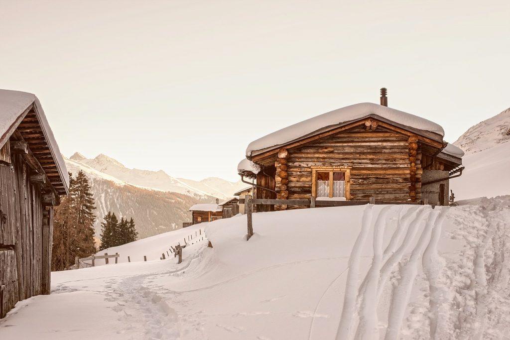 chalet de montagne en bois recouvert de neige